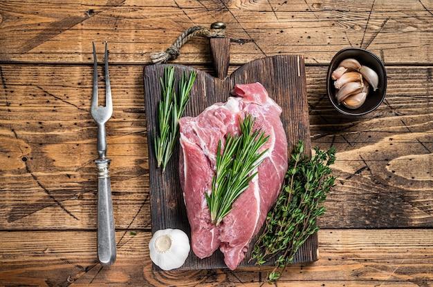 Frisches rohes schweineschulterfleisch mit zutaten und gewürzen auf hölzernem metzgerbrett. holztisch. draufsicht.