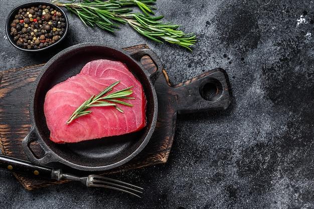 Frisches rohes thunfischsteak mit rosmarin in einer pfanne