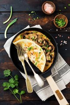 Frisches rührei, omelette oder frittata mit champignons, zwiebeln und frischen kräutern auf einer gusseisernen pfanne. draufsicht mit kopienraum.