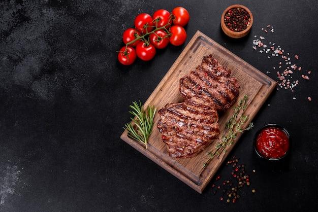 Frisches saftiges köstliches rindersteak auf einem dunklen hintergrund. fleischgericht mit gewürzen und kräutern