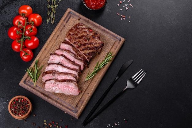 Frisches saftiges leckeres rindersteak auf dunkler oberfläche. fleischgericht mit gewürzen und kräutern