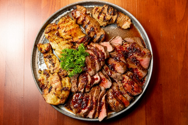 Frisches, saftiges sortiment an geschnittenem grillfleisch, das auf einem großen und runden teller liegt
