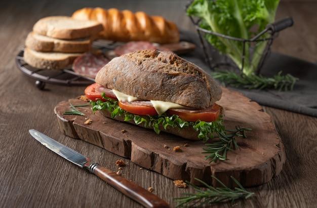 Frisches salamikäse sandwich mit tomate und grünem blattsalat
