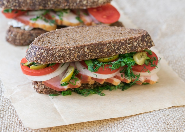 Frisches sandwich auf einem holztisch mit einem stück leinwand.