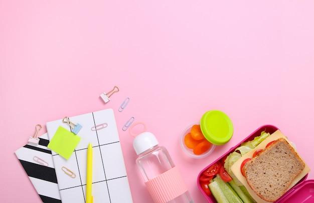 Frisches sandwich, kartoffel und gurke in rosa brotdose mit flasche wasser am büroarbeitsplatz. schließen sie oben vom gesunden snack im plastikbehälter an. gesundes nahrungsmittelkonzept. draufsicht, flache lage, rosa hintergrund.
