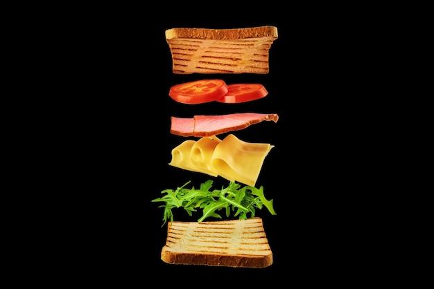 Frisches sandwich mit fliegenden zutaten auf dem schwarzen hintergrund lokalisiert. fliegenfutter-konzept