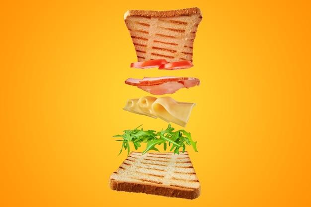 Frisches sandwich mit fliegenden zutaten auf gelb