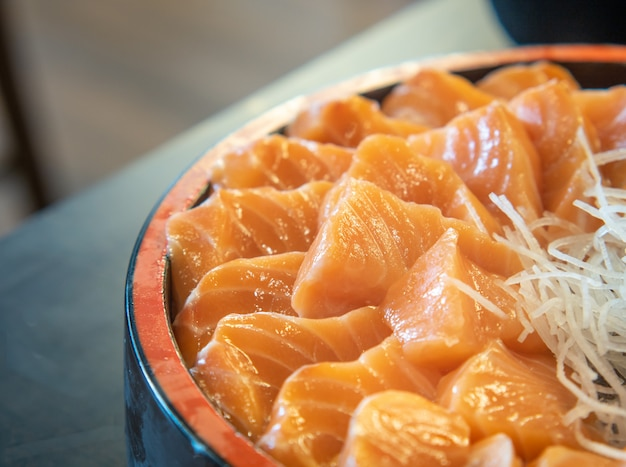 Frisches sashimi-lachsfilet in einer schüssel. japanisches gericht mit gemüse, selektiver fokus.