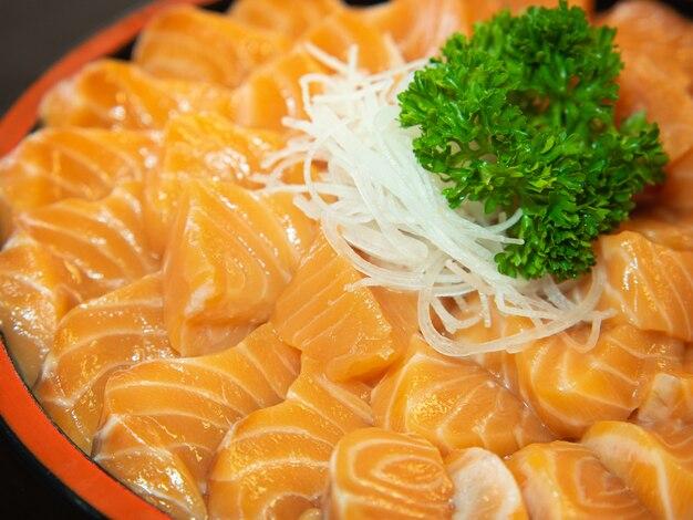 Frisches sashimi-lachsfilet in einer schüssel. japanisches gericht mit gemüse.