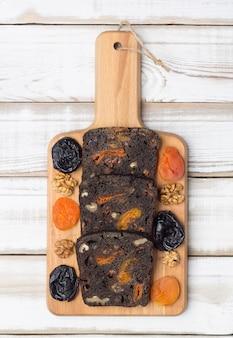Frisches schwarzes dessertbrot mit pflaumen, getrockneten aprikosen und walnüssen.