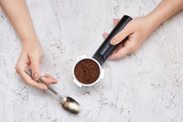Frisches schwarzes kaffeezubereitungskonzept, frauenhände auf weißem sperrholzhintergrund