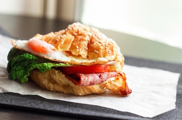 Frisches selbst gemachtes blt-sandwich mit speck-kopfsalat-tomaten-ei und hörnchen.