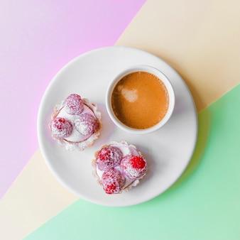 Frisches selbst gemachtes fruchttörtchen mit himbeer- und kaffeetasse auf platte