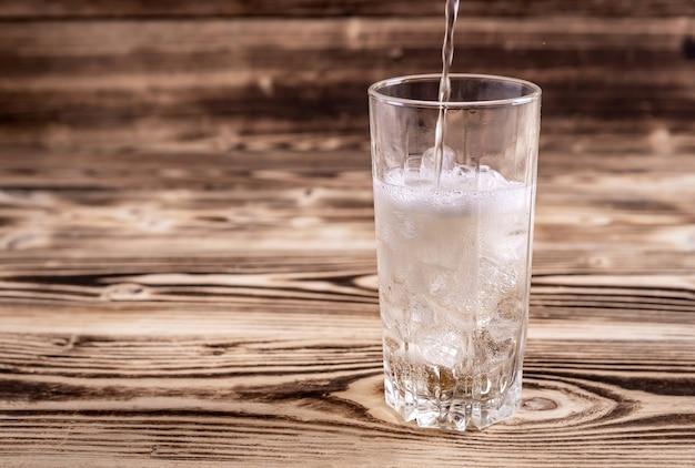 Frisches selterswasser wird mit eis in ein glas gegossen