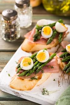 Frisches sendwich mit schinken-, spargel- und wachteleiern