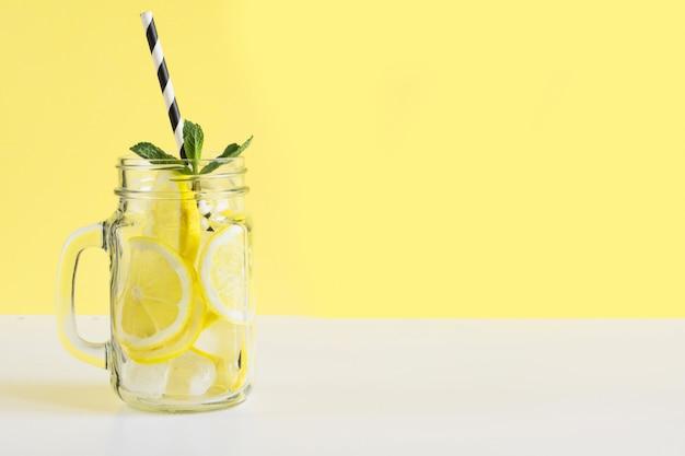 Frisches sommerfruchtwasser oder limonade mit zitrone und minze. nahansicht.