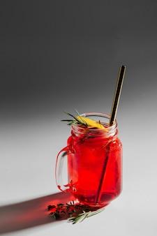 Frisches sommergetränk mit zitrusfrüchten, kräutern und eis in einem glas auf weißem hintergrund mit schatten