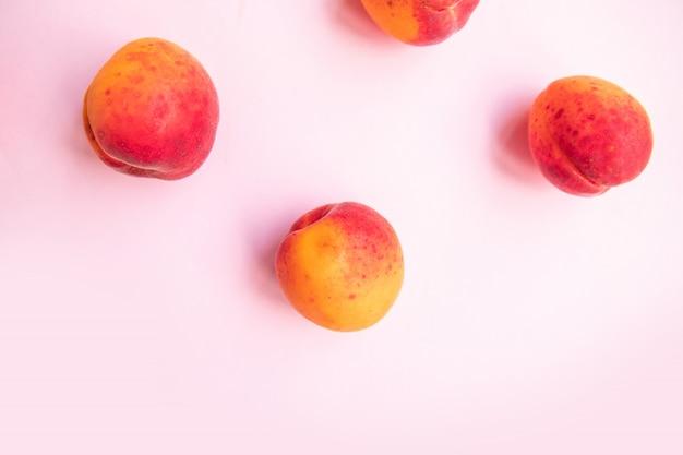 Frisches sommerobst. süße saftige pfirsiche der flachen zusammensetzung auf rosa hintergrund