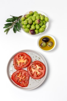 Frisches spanisches olivenöl extra vergine mit oliven und tomaten