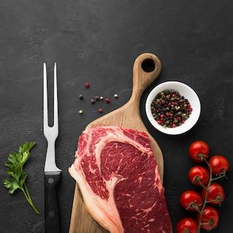 Frisches steak der draufsicht auf dem tisch mit kirschtomaten