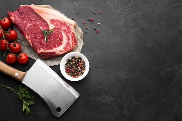 Frisches steak der draufsicht auf dem tisch mit tomaten