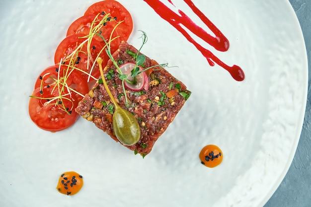 Frisches steak rindertartar mit kapern, gewürzen, zwiebeln auf einem weißen teller. nahansicht. draufsicht