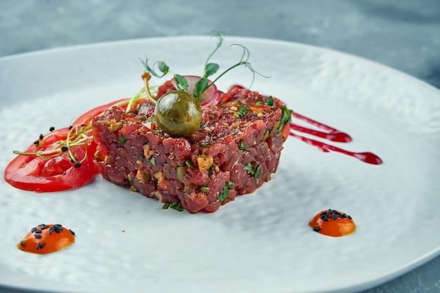 Frisches steak rindertartar mit kapern, gewürzen, zwiebeln auf einem weißen teller. nahansicht.