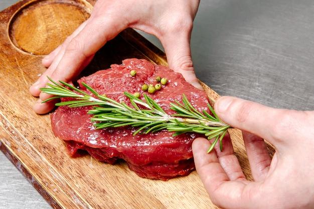 Frisches stück fleisch mit grüns auf einem hölzernen schneidebrett