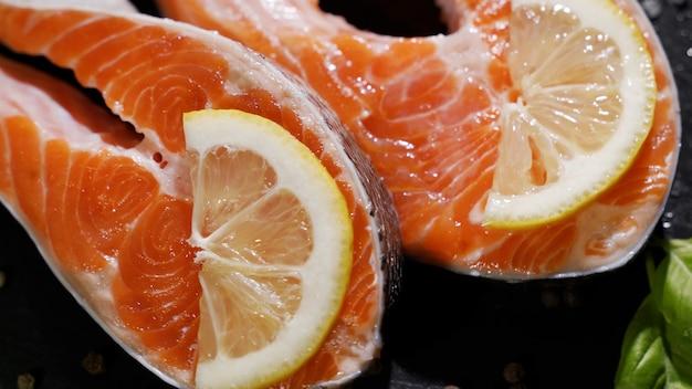 Frisches stück lachs auf schneidebrett auf küchentisch mit gewürzen zitrone gelegt