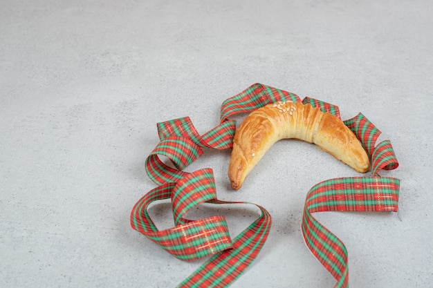 Frisches süßes croissant mit festlicher schleife auf weißer oberfläche.