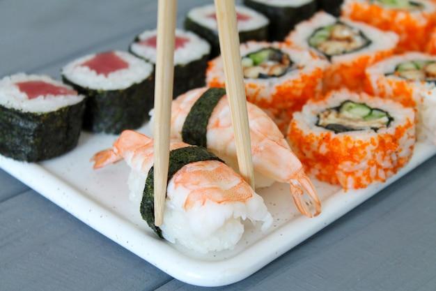 Frisches sushi-set maki und brötchen auf holztisch. essstäbchen halten nigiri mit garnelen