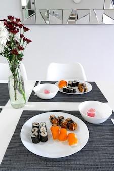 Frisches sushi und brötchen in einem weißen teller. sushi-mittagessen.