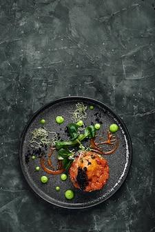 Frisches tartar mit lachs, avocado, rotem kaviar auf einem teller, schöne portion schöne portion, traditionelle italienische küche