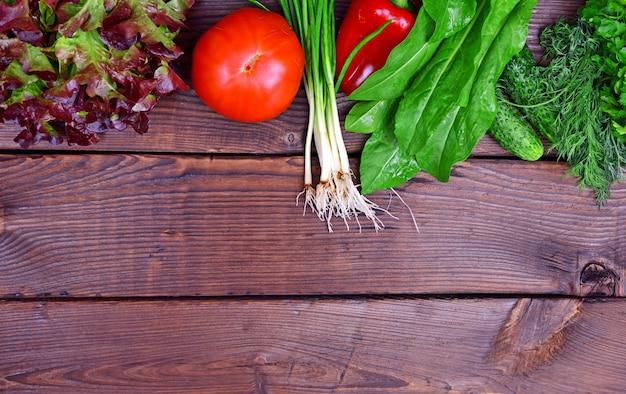 Frisches tomatengemüse, gurken und frühlingszwiebeln auf einem braunen hölzernen hintergrund