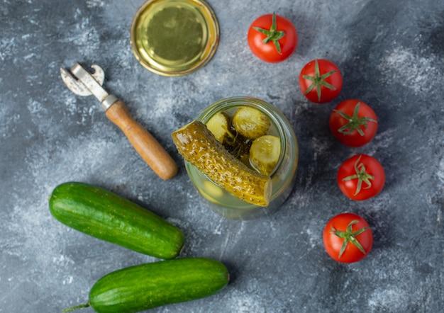 Frisches und eingelegtes gemüse. geöffnetes gurkenglas mit frischen tomaten und gurken