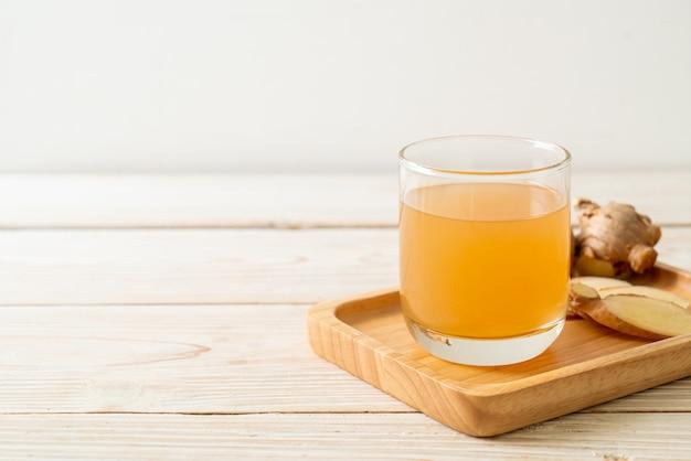 Frisches und heißes ingwersaftglas mit ingwerwurzeln - gesunde getränkeart