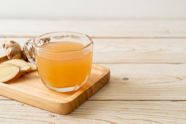 Frisches und heißes ingwersaftglas mit ingwerwurzeln. gesunder getränkestil