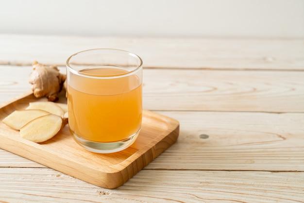 Frisches und heißes ingwersaftglas mit ingwerwurzeln - gesunder getränkestil