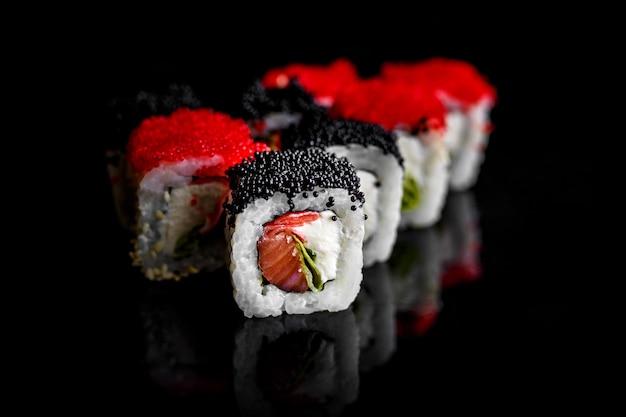 Frisches und köstliches maki-sushi lokalisiert auf schwarzem hintergrund.