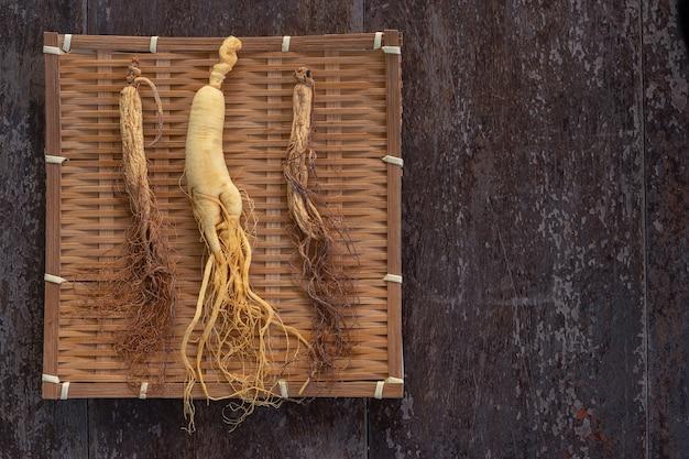 Frisches und trockenes ginseng auf bambuswebart mit kopienraum auf dem hölzernen hintergrund.