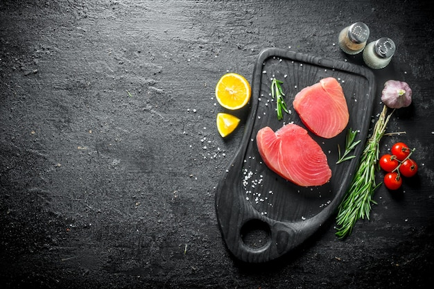 Frisches ungekochtes thunfischsteak auf einem schneidebrett mit tomaten, rosmarin, knoblauch, gewürzen und zitrone. auf schwarz rustikal