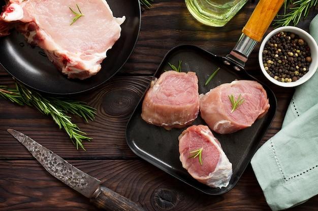 Frisches verschiedenes fleisch rohes schweinesteak und schnitzel auf gusseisernen pfannengewürzen und frischem rosmarin