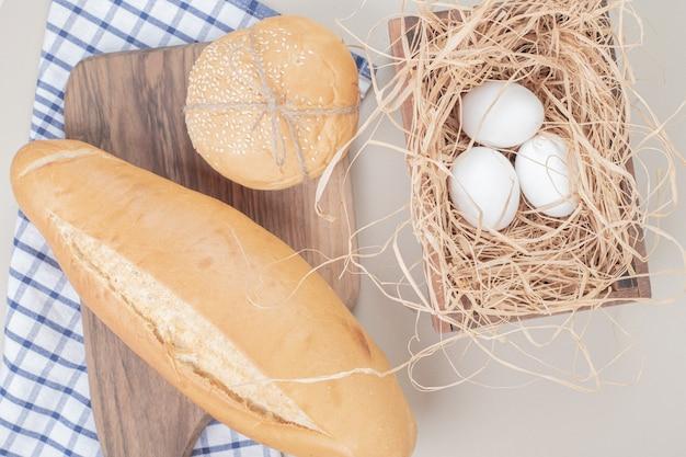Frisches weißbrot mit eiern auf tischdecke
