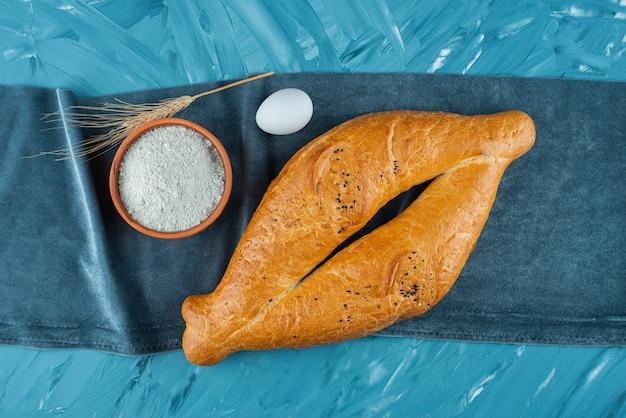 Frisches weißbrot mit einer tonschale salz und gekochtem weißem hühnerei.