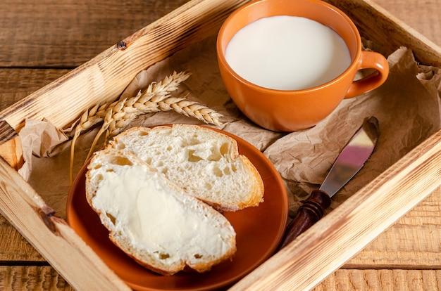 Frisches weizenmehlbrot mit butter und milch in einem tablett auf einem hölzernen hintergrund. frühstücks- und schlagzeugkonzept.