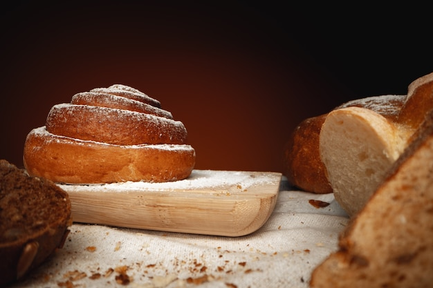 Frisches zimtbrötchen mit zuckerpulver auf holzbrett