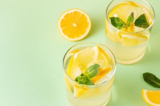 Frisches zitronenwasser mit minzblättern auf grünem hintergrund. zwei gläser sommergetränke mit kopienraum.