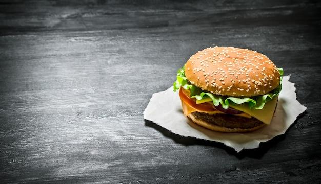 Frischfleisch burger mit gemüse. auf einer schwarzen tafel.