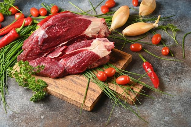 Frischfleisch mit bestandteilen für das kochen auf braunem hölzernem schneidebrett.