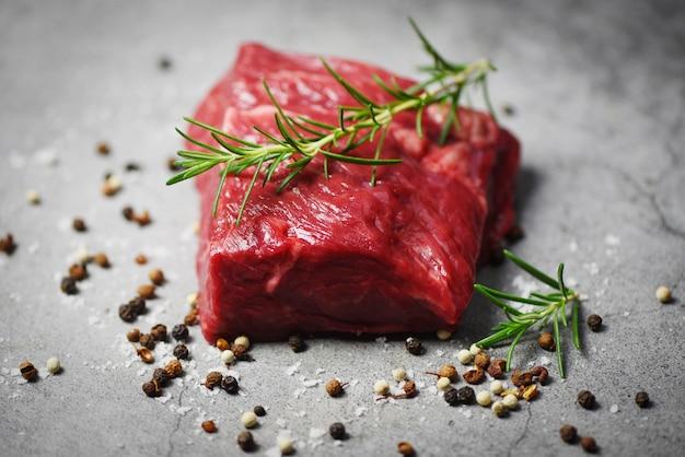 Frischfleischrindfleisch geschnitten auf schwarzem hintergrund - rohes rindfleischsteak mit kraut und gewürzen und rosmarin